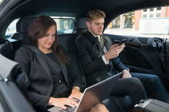 Young Businessman And Businesswoman Traveling In The Car Royalty Free Stock Images