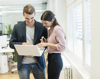 Young businessman and businesswoman using laptop in office Stock Photography