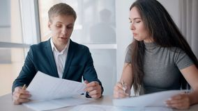 Young businessman and businesswoman working on project, talking at office desk. Young businessman and businesswoman working on project, talking at office desk stock video
