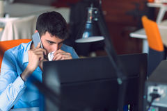 Young businessman busy working on laptop computer while talking on the smart-phone at office. Stock Photo
