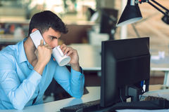 Young businessman busy working on laptop computer while talking on the smart-phone at office. Stock Image