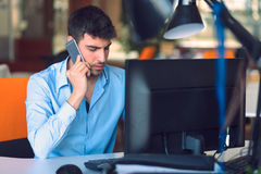 Young businessman busy working on laptop computer while talking on the smart-phone at office. Stock Photos