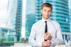 Young businessman buttoning cuff sleeves Stock Images