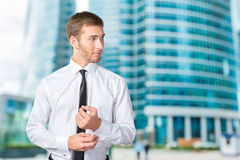 Young businessman buttoning cuff sleeves Royalty Free Stock Photography