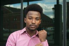 Young businessman buttoning cufflink hand pink shirt outside. Young man attaches his cufflink pink line shirt stock photos