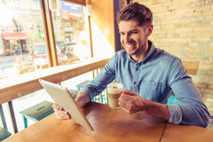 Young businessman in the cafe. Handsome young businessman is using a tablet, holding a cup of hot coffee drink and smiling while working in the cafe Royalty Free Stock Photo
