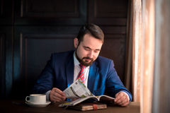 Young businessman in a cafe reading  magazine Royalty Free Stock Photography