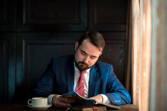 Young businessman in a cafe reading  magazine Royalty Free Stock Image