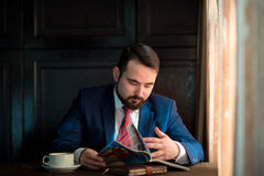 Young businessman in a cafe reading  magazine Stock Images