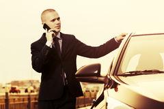 Young businessman calling on cell phone next to his car Stock Images