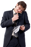 Young businessman calling by cellular phone. And writes in a notebook. Over white Stock Photos