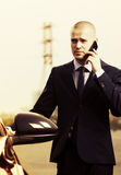 Young businessman calling on phone next to car Stock Photography