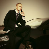 Young businessman calling on phone sitting on his car Stock Photos
