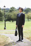 Young businessman carrying briefcase standing at park Royalty Free Stock Photos