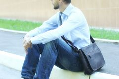 Young businessman in casual clothes with leather brief bag sitti stock photos