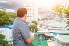 Young businessman in casual dress standing on transparent glass baclony and looking on city resort. Man holding glass of white vin stock image