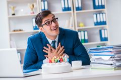 The young businessman celebrating birthday alone in office Stock Photography