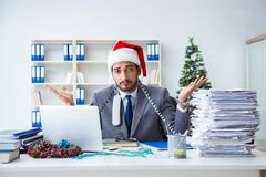 The young businessman celebrating christmas in the office. Young businessman celebrating christmas in the office Stock Photo