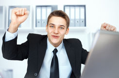 Young businessman celebrating his success. With arms raised at his workplace in bright office Royalty Free Stock Photos