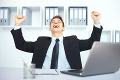 Young businessman celebrating his success. With arms raised at his workplace in bright office Royalty Free Stock Photo