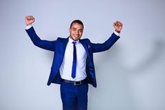 Young businessman celebrating success, expressing positivity sta. Nding on white background. Business, people and office concept royalty free stock photos