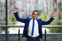 Young businessman celebrating success, expressing positivity whi. Le standing at the office building stock photos