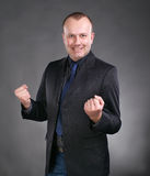Young businessman celebrating victory. Excited young businessman celebrating victory on a gray background stock photo