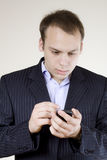 Young businessman with cellphone shocked Royalty Free Stock Photography