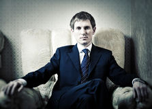 Young businessman on a chair. Contrast colors Royalty Free Stock Photo