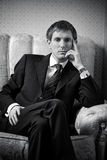 Young businessman on a chair. Black and white Royalty Free Stock Image