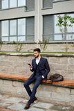 Young businessman checking his mobile phone outdoors Stock Photo