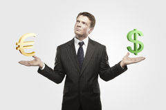Young businessman chooses euro or dollar signs. On a gray background royalty free stock photos