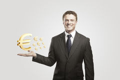 Young  businessman chooses a Gold Euro Signs. Royalty Free Stock Image