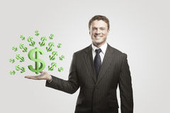 Young  businessman chooses a green US dollar signs. On a gray background Stock Photography