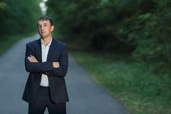 Young businessman in a classic suit with folded hands standing on the road in forest and looking at camera. Copyspace Royalty Free Stock Image