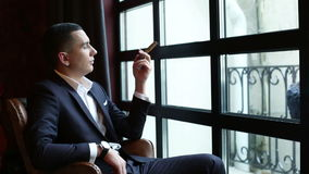 Young businessman in a classic suit sitting in front of the window with cigar in left hand.