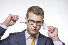 Young businessman cleaning his ears with a cotton tissue. Young man cleaning his ears to avoid deafness Royalty Free Stock Photo