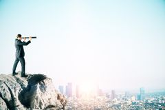 Businessman with telescope. Young businessman on cliff looking into the distance on blue sky background with city skyline and copy space. Research and vision royalty free stock image