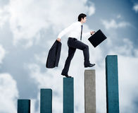 Young businessman climbing grey and blue steps Royalty Free Stock Images