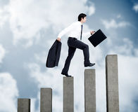 Young businessman climbing grey steps Royalty Free Stock Photos