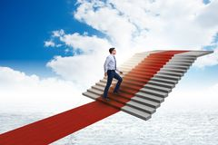 The young businessman climbing stairs and red carpet into sky. Young businessman climbing stairs and red carpet into sky Royalty Free Stock Images