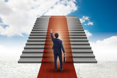 The young businessman climbing stairs and red carpet into sky. Young businessman climbing stairs and red carpet into sky Royalty Free Stock Image
