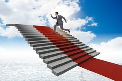 The young businessman climbing stairs and red carpet into sky Royalty Free Stock Images