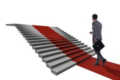 Young businessman climbing stairs and red carpet on white backgr. Ound Royalty Free Stock Photography