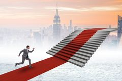 The young businessman climbing stairs and red carpet Stock Image