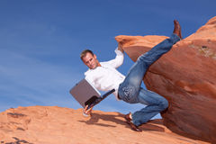 Young businessman climbing up with his laptop Royalty Free Stock Image