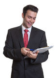 Young businessman with clipboard making notes Stock Photo