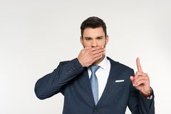 Young businessman closing mouth with palm and pointing up with finger. Isolated on grey Royalty Free Stock Images