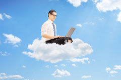 Young businessman on clouds working on a laptop Stock Photo
