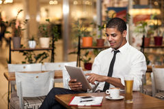 Young businessman in the coffee break working on his ipad Royalty Free Stock Photos
